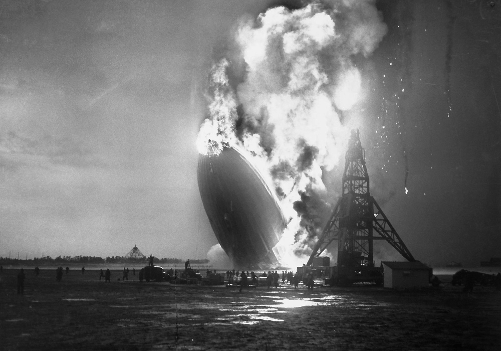 06 May 1937, Lakehurst, New Jersey, USA --- Original caption: As Flaming Zep Settled to Earth. Lakehurst, N.J.: Members of the landing crew are shown fleeing from beneath the dirigible Hindenberg as the flaming craft, a greasy pall of smoke marking its last train, falls to the Lakehurst Landing Field. Over to the left of the photo, rescue workers, despite the hail of flaming embers, rush toward the wreck. More than fifty persons, including members of the landing crew are believed dead in the air disaster. The accident occurred as the Hindenberg was landing after its first trip to Germany. --- Image by © Bettmann/CORBIS